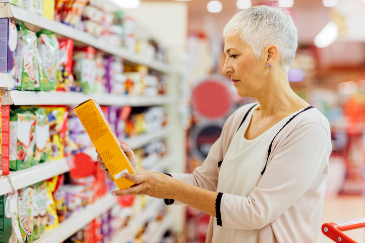 woman checking food label for whole grains